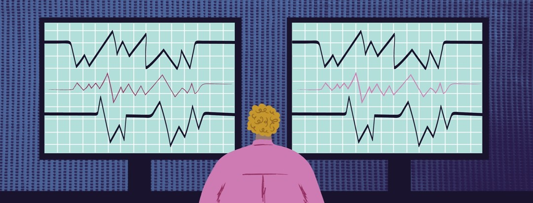 a sleep technologist looking at two large computer screens showing lots of data