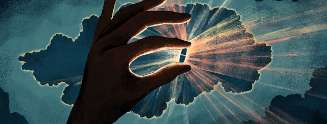 A hand in shadow holds up a pill that is illuminated from behind, emitting rays of light
