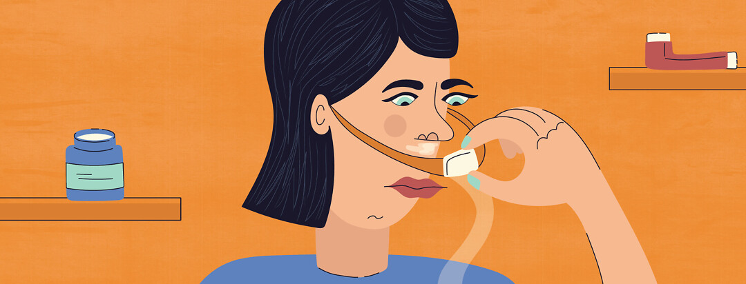 a woman pulls back her CPAP mask to apply vapor rub under her nose